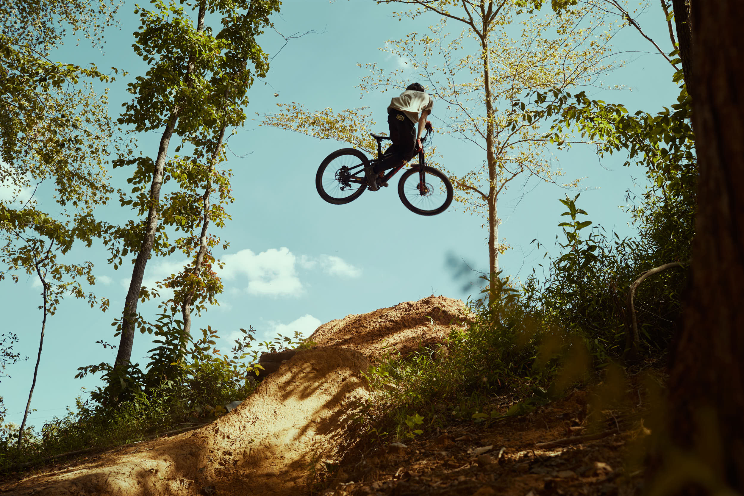 Cooper Rodrigues, downhill biker, jumping a hand-dug ramp in Raleigh, NC.